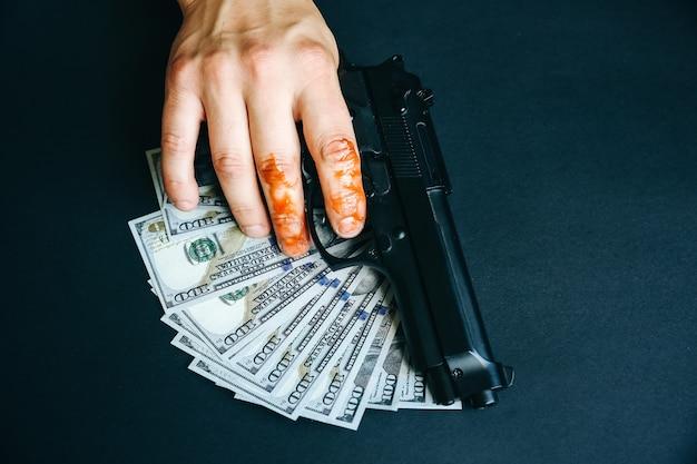 Mężczyzna z ręką we krwi trzyma broń. źle zdobyte pieniądze na stole. skradzione dolary. zabójca koncepcja kryminalna.