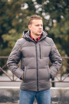 Mężczyzna z rękami w kieszeniach na zewnątrz w kurtce zimowej