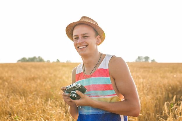 Mężczyzna z retro aparatem fotograficznym moda podróże styl życia na zewnątrz