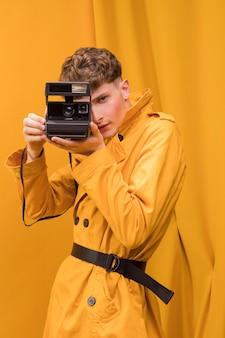 Mężczyzna z retro kamerą w żółtej scenie