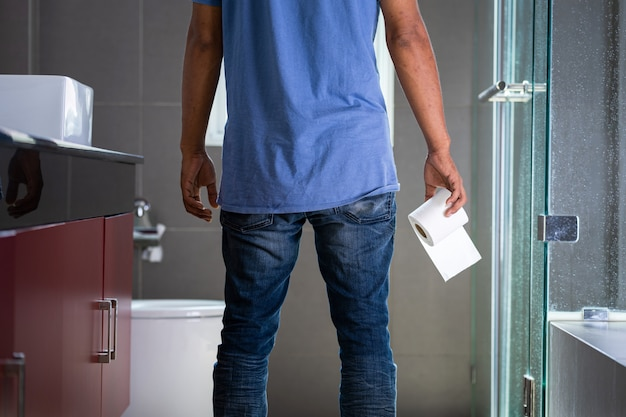 Mężczyzna z rolką papieru toaletowego w toalecie
