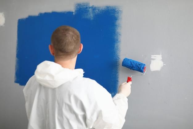 Mężczyzna z rolownikiem w jego rękach maluje ścianę w błękicie.
