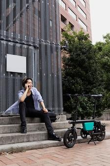 Mężczyzna z rowerem elektrycznym w mieście rozmawia przez telefon