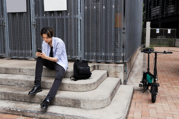 Mężczyzna z rowerem elektrycznym w mieście za pomocą smartfona