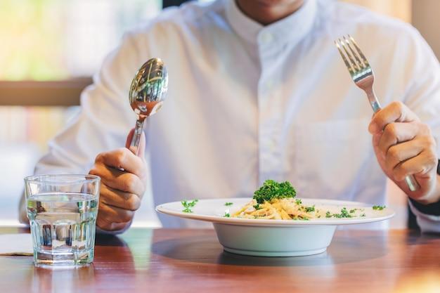 Mężczyzna z rozwidleniem i łyżką przygotowywającymi jeść spaghetti carbonara w talerzu na stole z szkłem woda