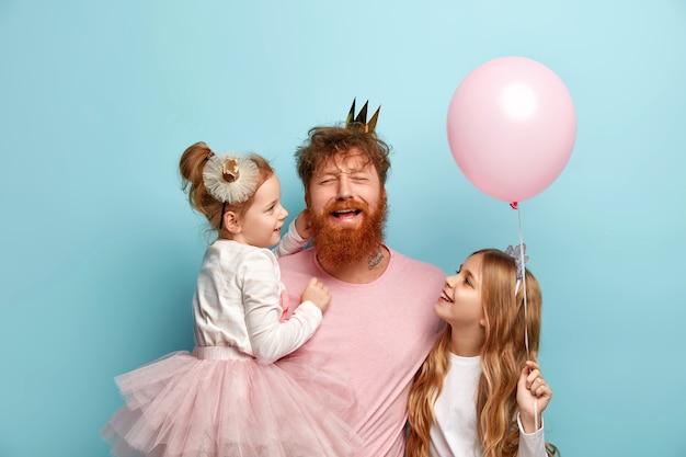 Mężczyzna z rudą brodą i córkami z akcesoriami na przyjęcie