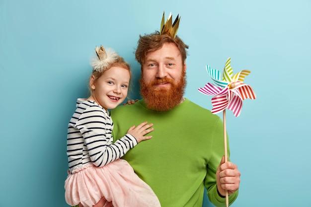 Mężczyzna z rudą brodą i jego córką z akcesoriami imprezowymi