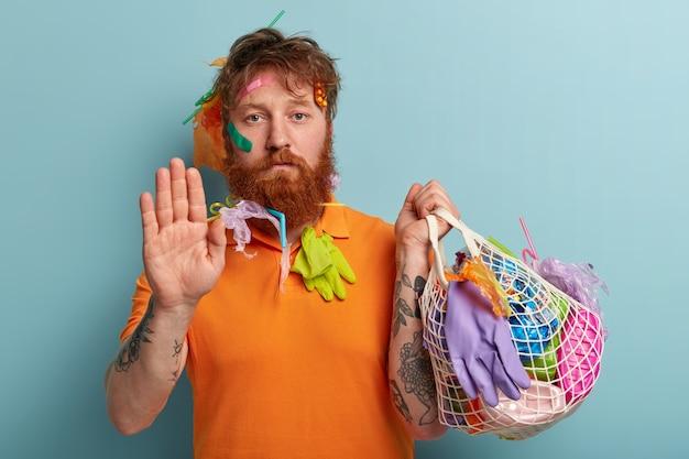 Mężczyzna z rudą brodą trzyma worki z plastikowymi odpadami