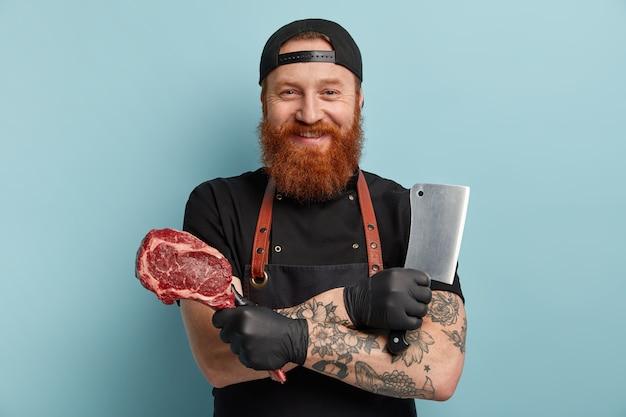 Mężczyzna z rudą brodą w fartuchu i rękawiczkach, trzymając nóż i mięso