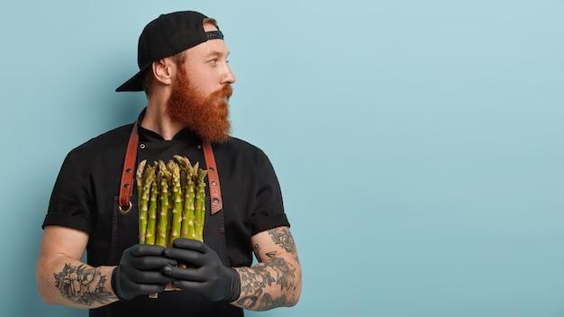 Mężczyzna z rudą brodą w fartuchu i rękawiczkach, trzymając szparagi