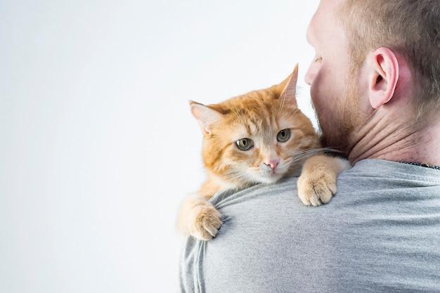 Mężczyzna z rudym kotem w ramionach