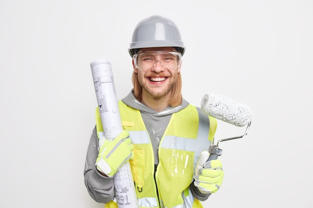 Mężczyzna z rudymi włosami trzyma papierowy plan i wałek do malowania ubrany w ochronny kask ochronny przezroczyste okulary jednolite na białym tle