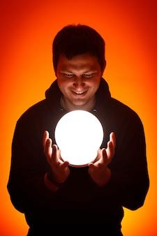 Mężczyzna z świecącą piłką w rękach.