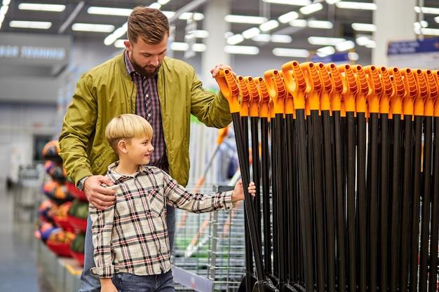 Mężczyzna z synem wybiera łopatę do ogrodu w sklepie, chce ją kupić, pracowity mężczyzna uczy syna żyć dobrze