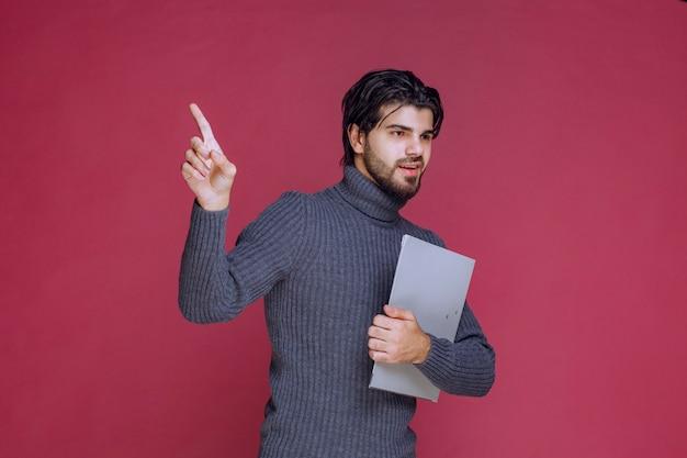 Mężczyzna z szarą teczką sprawia, że jego wskazujący palec w górę.