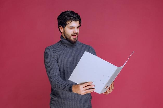 Mężczyzna z szarym folderem czyta raporty.