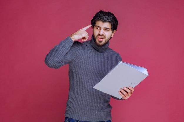 Mężczyzna z szarym folderem dyskutuje z kolegami podczas sprawdzania.