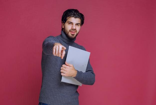 Mężczyzna z szarym folderem omawia to z kolegami podczas sprawdzania.