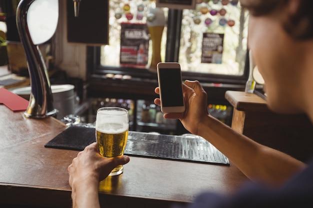 Mężczyzna z szkłem piwo używać telefon komórkowego w kontuarze
