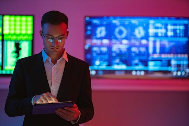 Mężczyzna z tabletem stojącym na tle ekranu