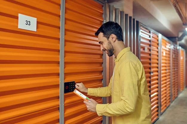 Mężczyzna z tabletem w pobliżu zamka szyfrowego drzwi garażowych