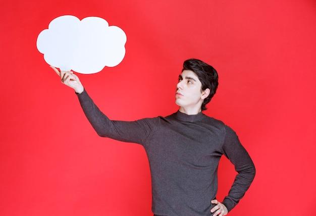 Mężczyzna z tablicą informacyjną w kształcie chmury nad głową
