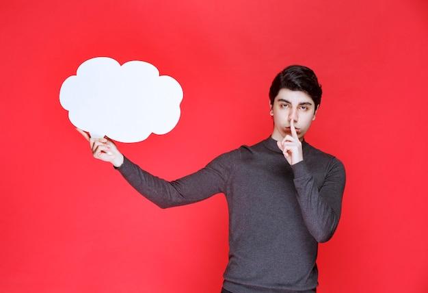 Mężczyzna z tablicą informacyjną w kształcie chmury proszący o ciszę