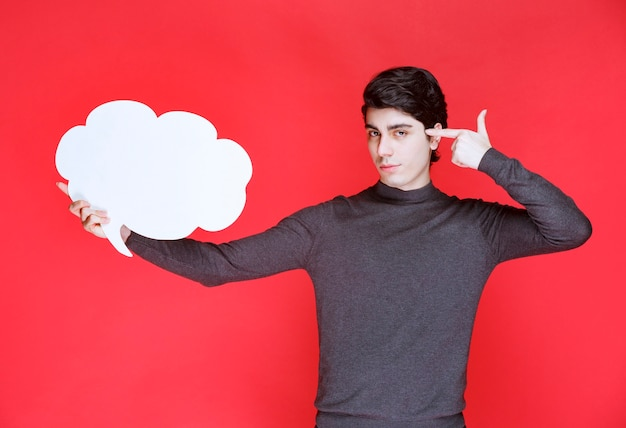 Mężczyzna z tablicą informacyjną w kształcie chmury, wskazującą gdzieś