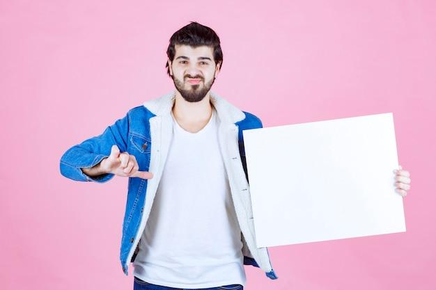 Mężczyzna z tablicą myślową o kwadratowym kształcie wygląda na zamyślonego i niezadowolonego