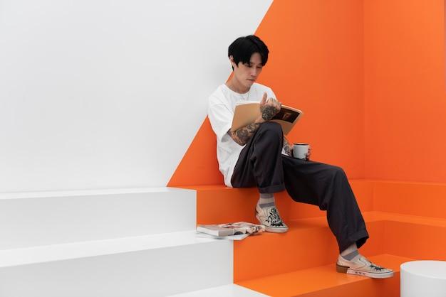Mężczyzna z tatuażami, cieszący się filiżanką kawy w kawiarni i czytający książki
