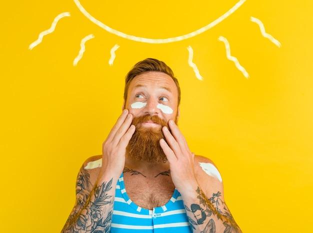 Mężczyzna z tatuażami i kostiumem kąpielowym nakłada filtr przeciwsłoneczny