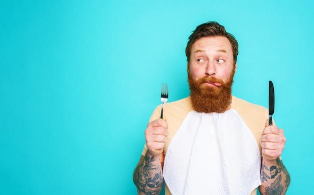 Mężczyzna z tatuażami jest gotowy do jedzenia ze sztućcami w ręku na cyjan