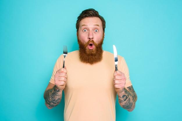Mężczyzna z tatuażami jest gotowy do zjedzenia czegoś ze sztućcami w ręku.