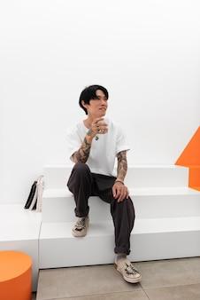 Mężczyzna z tatuażami przy filiżance kawy w kawiarni