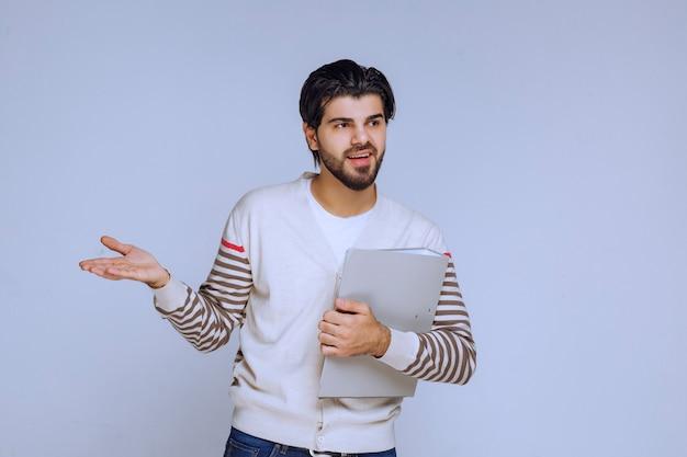 Mężczyzna z teczką z raportami i wskazujący kogoś po lewej stronie.
