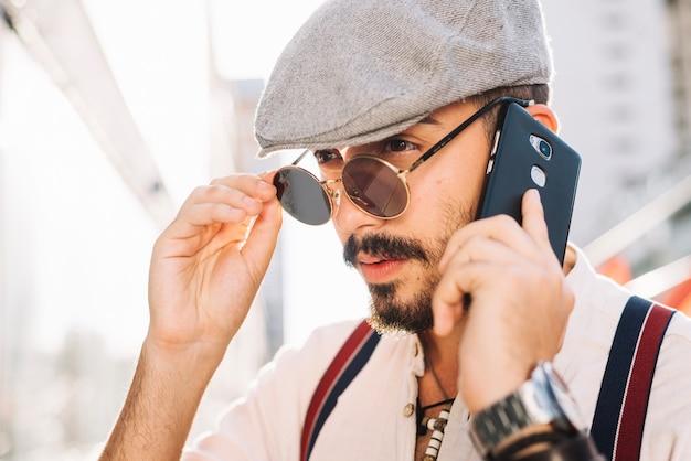 Mężczyzna z telefonem bierze daleko okulary przeciwsłonecznych