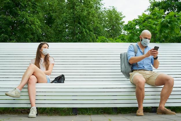 Mężczyzna z telefonem i młoda kobieta siedzą na przeciwległych końcach ławki, zachowując odległość od siebie, aby uniknąć rozprzestrzeniania się koronawirusa.
