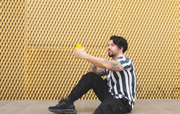 Mężczyzna z telefonem komórkowym robi selfie na złotym tle