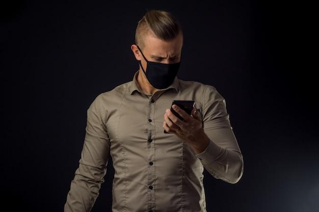Mężczyzna z telefonem nad czerni ścianą