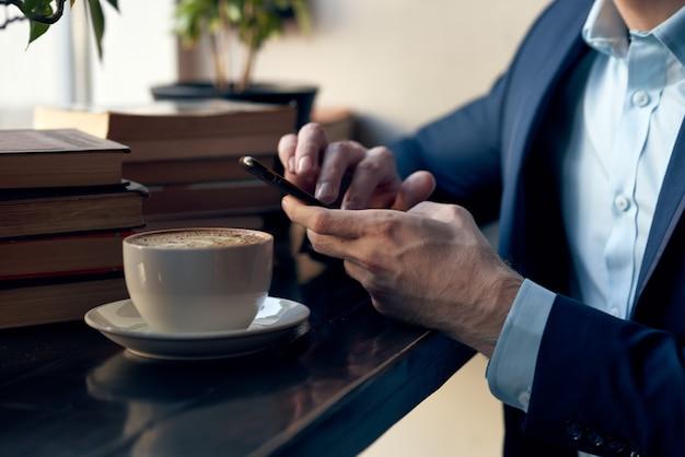 Mężczyzna z telefonem w dłoniach siedzi w kawiarni wypoczynek praca styl życia biznesmen