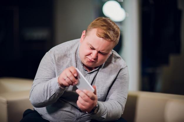 Mężczyzna z telefonem zaskakuje jak bawić się gry siedzi na kanapie w biurze