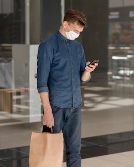 Mężczyzna z torbą na zakupy czyta wiadomość na swoim smartfonie.