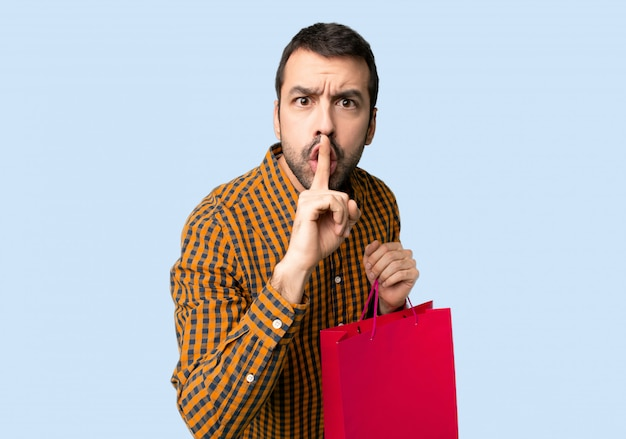 Mężczyzna z torba na zakupy pokazuje znaka cisza gesta kładzenia palec w usta na odosobnionym błękitnym tle