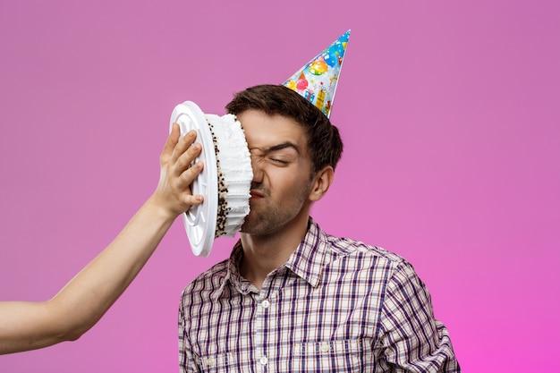 Mężczyzna z tortem na twarzy nad purpury ścianą. przyjęcie urodzinowe.