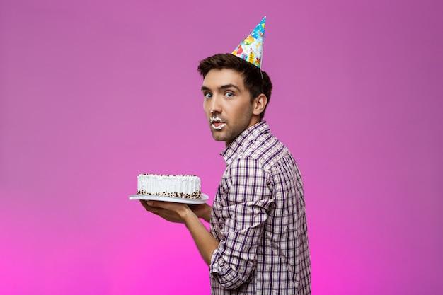Mężczyzna z tortem na wargach nad purpury ścianą. przyjęcie urodzinowe.