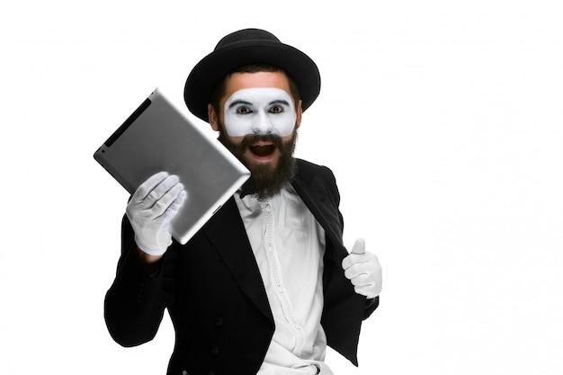 Mężczyzna z twarz mimem pracuje na laptopie odizolowywającym na bielu