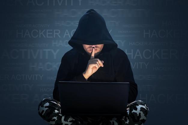 Mężczyzna z ukrytą twarzą pracujący przy komputerze. trzymając palec na ustach. haker kradnący dane z koncepcji laptopa w celu zapewnienia bezpieczeństwa sieci, kradzieży tożsamości i przestępczości komputerowej