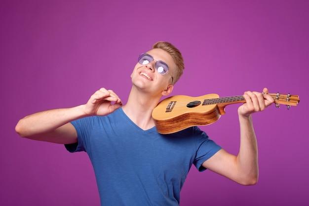 Mężczyzna z ukulele w rękach na fioletowym tle gra jak na skrzypcach