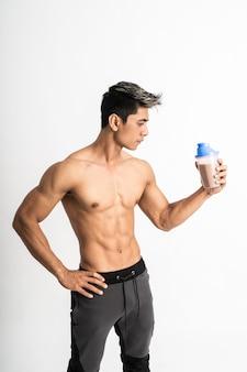 Mężczyzna z umięśnionym ciałem trzymającym butelkę jedną ręką na talii stoi twarzą do boku
