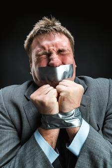 Mężczyzna z ustami zakrytymi taśmą maskującą